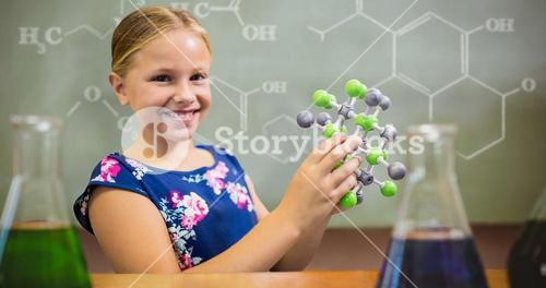 Composite image of young girl smiling while holding molecular structure