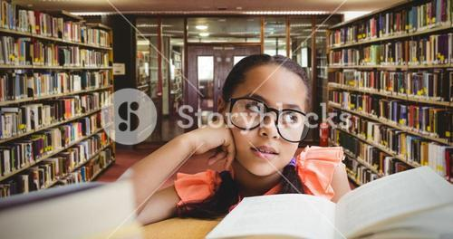 Composite image of young girl day dreaming by book at table