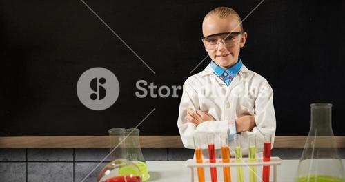 Composite image of boy standing in front of table with laboratory equipment