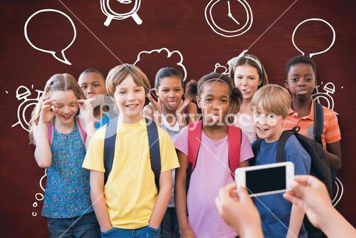 Composite image of cute pupils using mobile phone