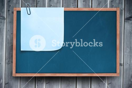 Composite image of blue sticky note with paper clip