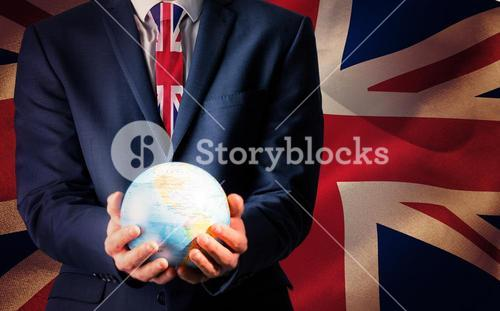 Composite image of hand of businessman holding terrestrial globe