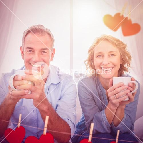 Composite image of smiling middle aged couple sitting on the couch having coffee