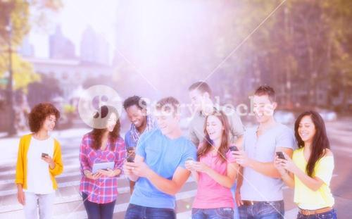 Composite image of four laughing friends sending texts on their phones