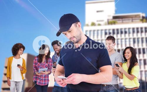 Composite image of smiling man using mobile phone