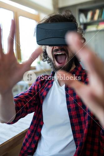 Excited man using virtual reality headset