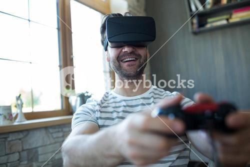 Happy man using virtual reality headset and playing video game
