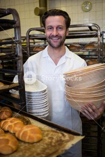 Portrait of smiling baker holding stack of tray and boxes