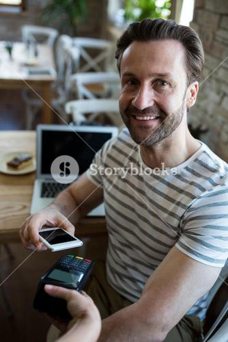 Smiling man paying with NFC technology on mobile phone