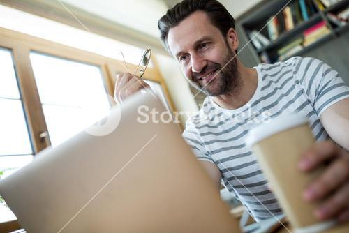 Man looking at laptop in coffee shop