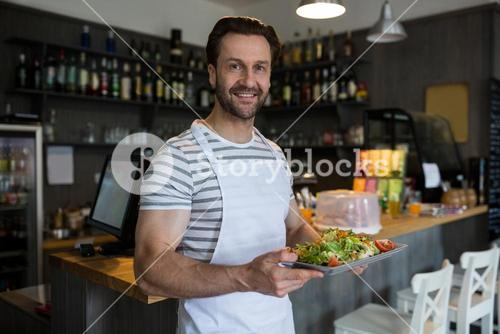 Smiling waiter carrying a tray of salad in restaurant