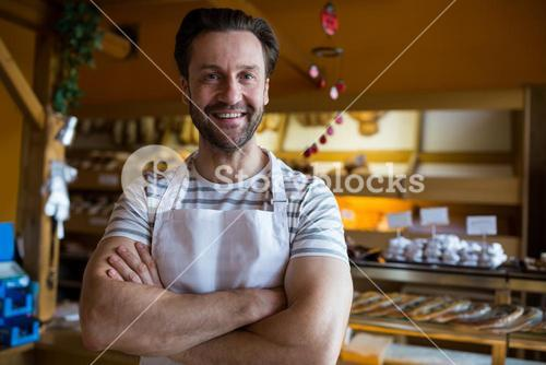 Portrait of smiling owner standing in bakery shop