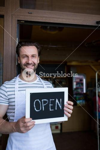Smiling owner holding a open sign at bakery shop entrance