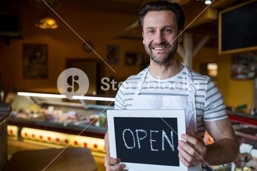 Smiling owner holding a open sign in the bakery shop