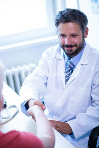 Doctor shaking hands with patient in medical office
