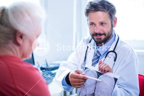 Doctor explaining to patient about x-ray in medical clinic