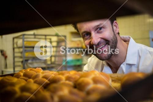 Smiling baker removing baked bun from oven