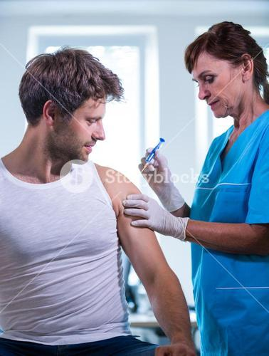 Female doctor giving an injection to a patient