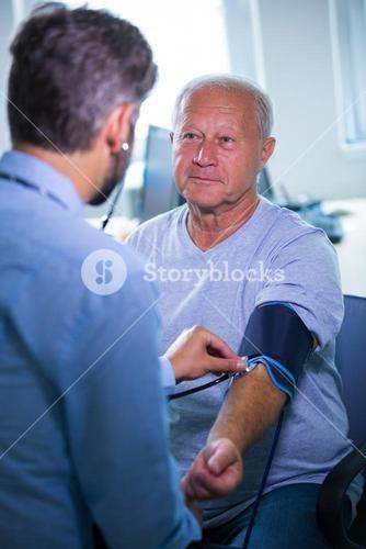 Male doctor checking blood pressure of patient
