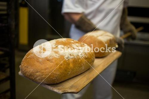 Baker removing baked buns from oven