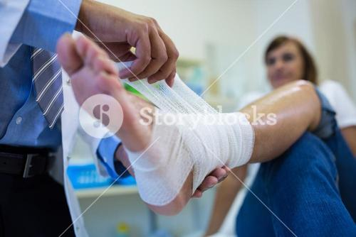 Male doctor bandaging foot of female patient