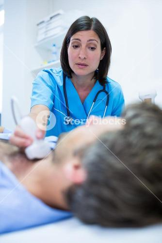 Male getting ultrasound of a thyroid from doctor