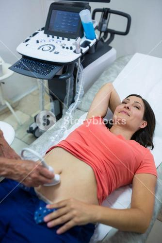 Woman getting ultrasound of a abdomen from doctor