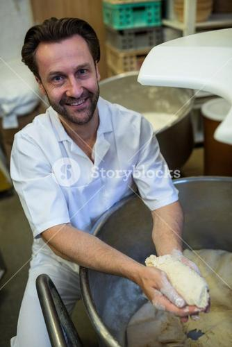 Smiling baker preparing dough