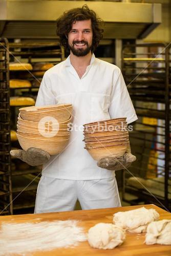 Smiling baker holding stack of bowls while preparing dough