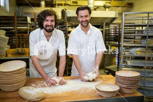 Two smiling bakers kneading dough