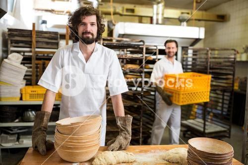 Two smiling bakers working in bakery kitchen