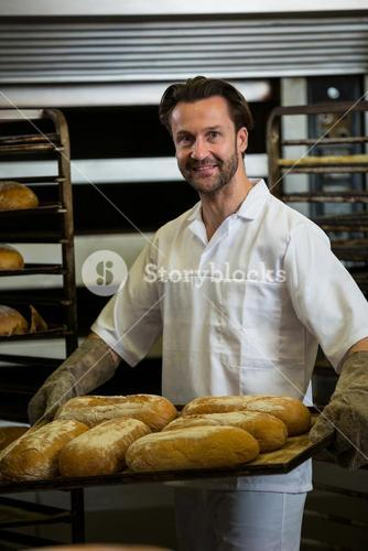 Smiling baker carrying a tray of baked buns