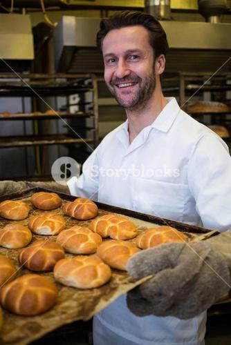 Smiling baker holding a tray of freshly baked buns