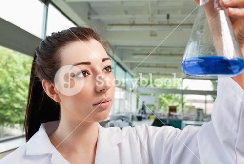 Brunette looking at an Erlenmeyer flask