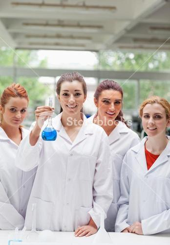 Portrait of lab partners posing with a flask