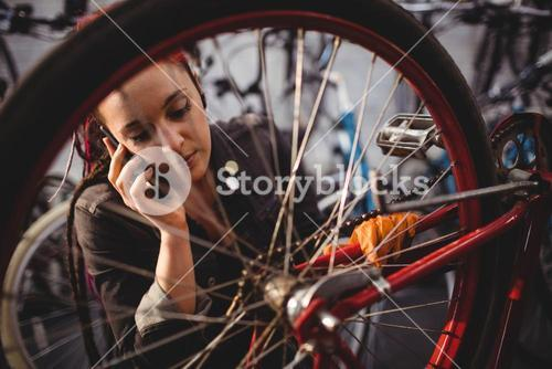 Mechanic talking on mobile phone while repairing bicycle
