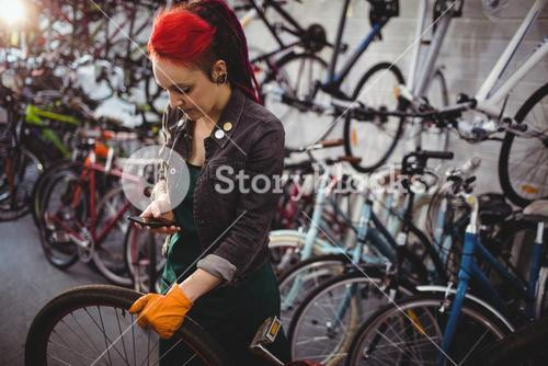 Mechanic using mobile phone while repairing bicycle