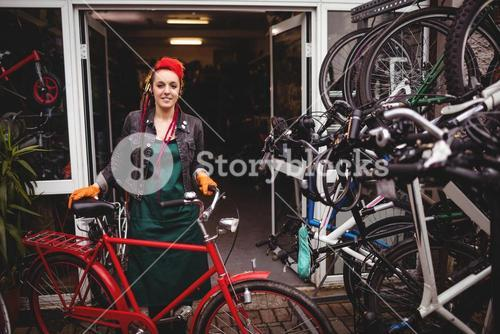 Smiling mechanic standing with a bicycle in workshop
