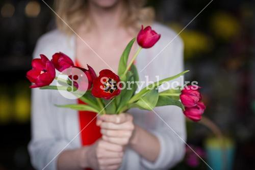 Female florist holding bunch of flower in flower shop