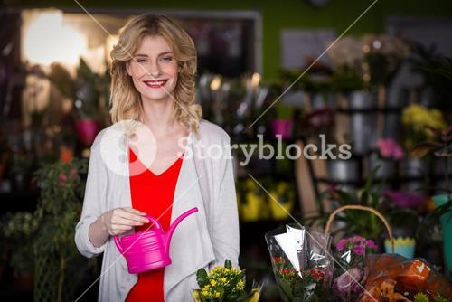 Happy female florist holding a watering can in flower shop