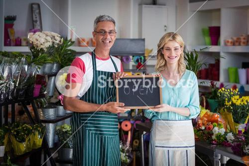 Smiling florists holding open sign on slate in flower shop