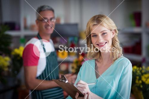 Smiling female florist noting on clipboard at flower shop