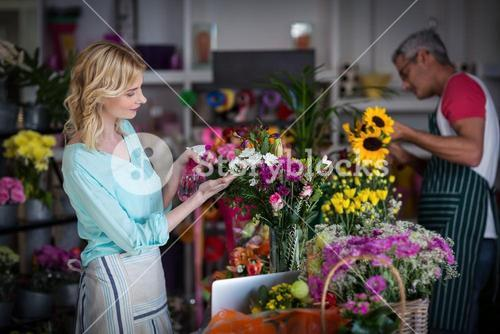 Florists spraying water on flowers in flower shop