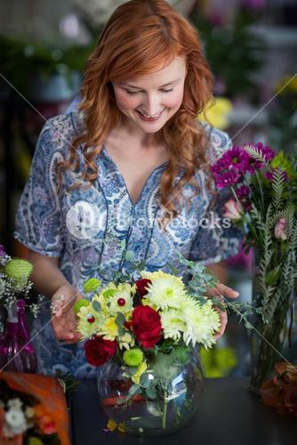 Female florist checking a flowers arrangement in vase