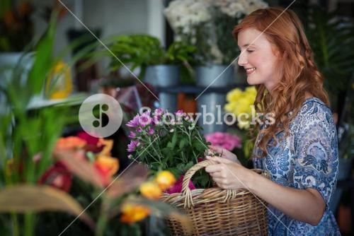 Female florist holding basket of flowers