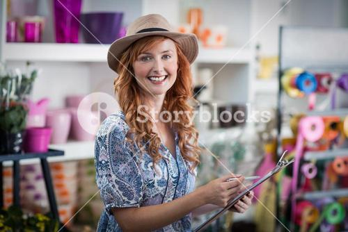 Smiling female florist noting on clipboard