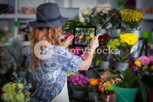 Female florist taking photograph of flowers