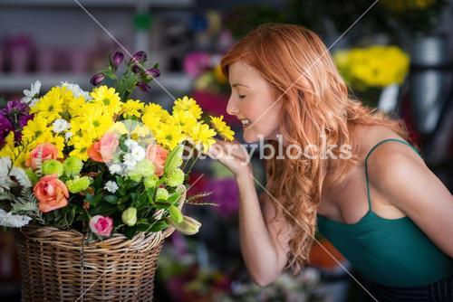 Female florist smelling flower