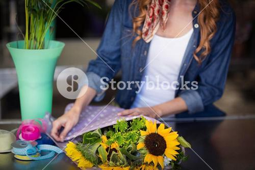 Female florist wrapping flower bouquet