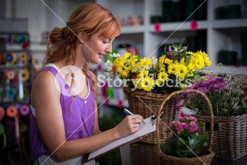 Female florist writing on the clipboard